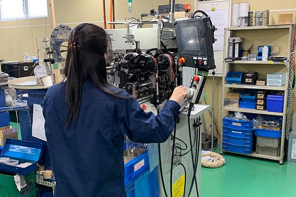 工場で装置を操作するスタッフ1